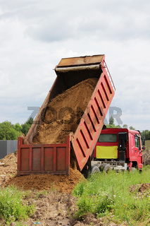 Construction truck unloads sand at the site of repair where laying the pipeline with water. Yellow empty advertising awning on the cab