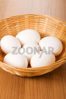 Many white eggs on the wooden table