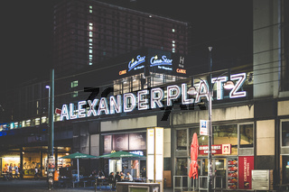 Illuminated letters of the Alexanderplatz train station exterior at night in Berlin