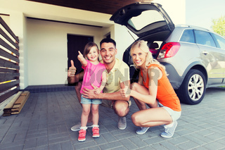 happy family with car showing thumbs up at parking