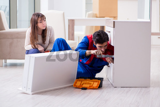 Contractor repairman assembling furniture under woman supervisio
