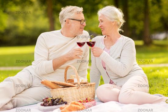 happy senior couple having picnic at summer park