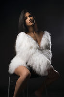 Beautiful brunette in white fur coat on a chair