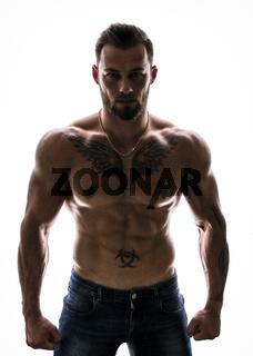 Attractive shirtless muscleman on dark background