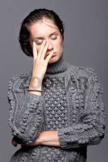 Beauty portrait of young woman in gray wool sweater. Brunette girl with bright blue eyes and day female makeup