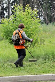 Worker in uniform mows the grass trimmer.
