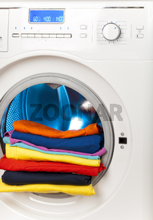 The washing machine with an open door and linen