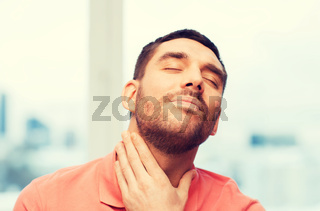 unhappy man suffering from throat pain at home