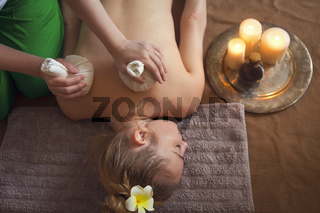 Woman getting thai herbal compress massage in spa