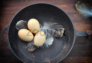 Three chicken eggs in a shell in a black cast-iron frying pan,