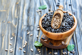 Sunflower seeds and a scoop in wooden bowl.
