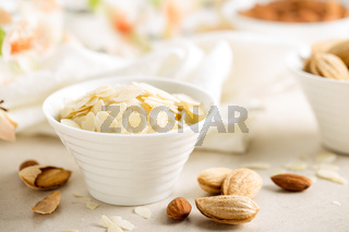 Almond nuts shavings in a bowl on white background, healthy eating