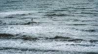 Sihouette of a stand up paddle surfer in a rough ocean in Daimus, Spain