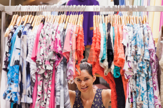 Woman standing behind a clothes rack smiling