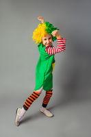 The little girl in a clown uniform has fun
