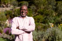 Portrait of happy african american senior man taking photo outdoors
