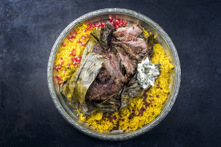 Slow cooked Omani lamb shuwa coated in rub of spices and wrapped in banana leaves served with rice and yoghurt as top view on a rustic oriental tray