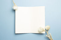 Open notebook with white dry flowers on blue background. top view, copy space
