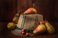 pears in bulk on an old hat on a dark wooden background in a rustic style