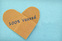Bandage in a heart shape with 100% Vaxxed text -- COVID-19 vaccine concept