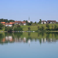 Rural village Seegraeben mirroring in Lake Pfaeffikon.