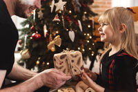 Father gives New Year or Christmas gift or present to his smiling happy daughter