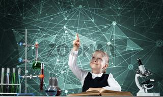 Little girl scientist sitting at desk