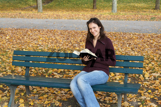 junge Frau mit Buch in Herbstszene