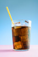 A glass of cola with ice on blue and pink background