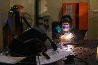 Professional welder performs work with metal parts in factory, sparks and electricity. Industry worker banner.