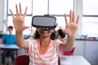 African american girl wearing vr headset gesturing while sitting on her desk in the class at school