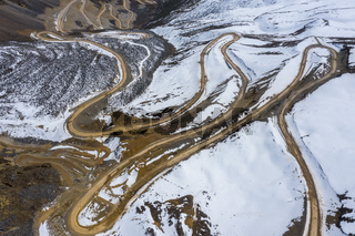 aerial view of the winding dirt road on snow mountain