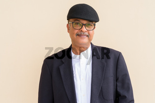 Portrait of handsome Indian businessman with mustache wearing hat against plain wall