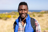 Portrait of fit african american man wearing backpack hiking on coast