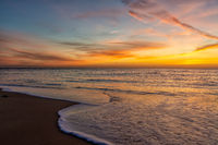 gorgeous colorful sunset over the ocean and beach with gentle waves lapping at the shore
