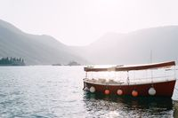 Pleasure red motor boat with a sun awning on the water of the Bay of Kotor.