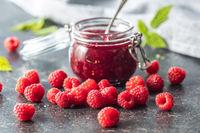 Red rasberries jam in jar and ripe raspberries.