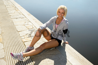 Sport woman relax on pier sitting water