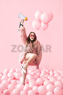 Trendy smiling woman holding megaphone on pink balloons background