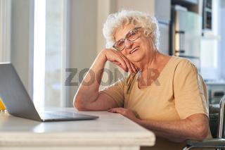 Seniorin am Computer freut sich über online Kommunikation