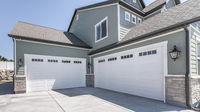 Pano Exterior of a house with concrete driveway and two closed white garage doors with windows