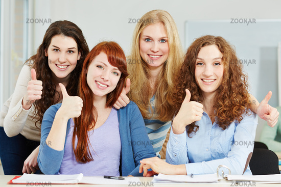 Frauen halten Daumen hoch in der Uni