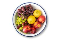 white enamel bowl with blue rim filled with fresh fruits