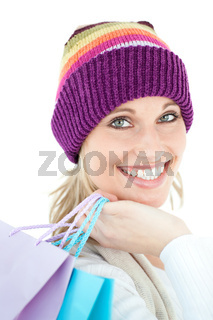 Bright woma holding shopping bags wearing a colourful hat against white background