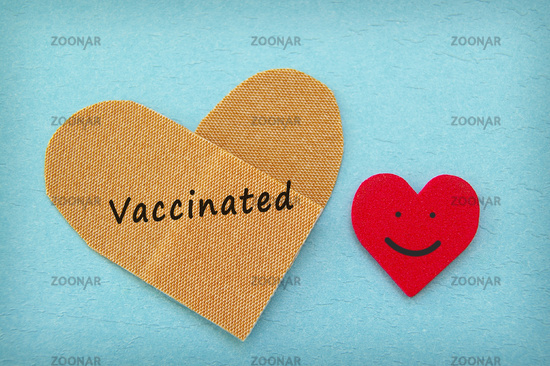 Vaccinated text on a heart shaped bandage with red smiling heart