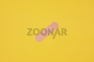 adhesive plaster tape or medical strip on yellow background