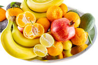 Assorted fruit and vegetable platter of bananas, pomegranate, lemon, tangerine and avocado.