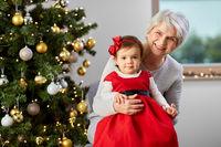 grandmother and baby girl with at christmas tree