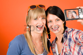 Two young woman friends taking picture smiling