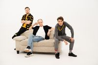 Friends seated on couch in studio. Three stylish young guys talking on the camera. Group of friends are sitting on a soft couch and communicates isolated on white background